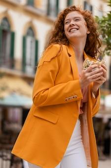 Счастливая рыжая женщина ест уличную еду