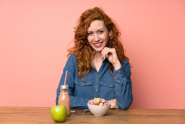 Happy redhead woman having breakfast
