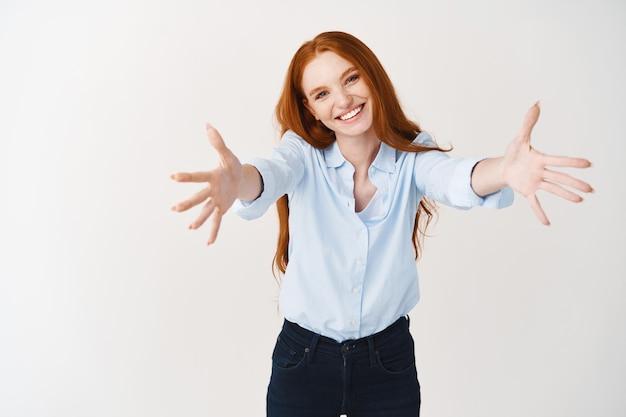 행복한 빨간 머리 여성 매니저가 당신을 안기 위해 앞으로 손을 뻗습니다. 생강 머리를 한 귀여운 여성이 팔짱을 끼고 흰 벽 위에 서 있다