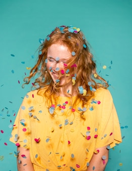 Donna felice della testarossa che fa festa con i coriandoli tra i capelli