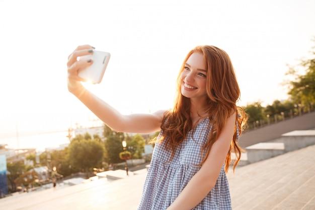 Счастливый рыжий женщина с длинными волосами, принимая селф