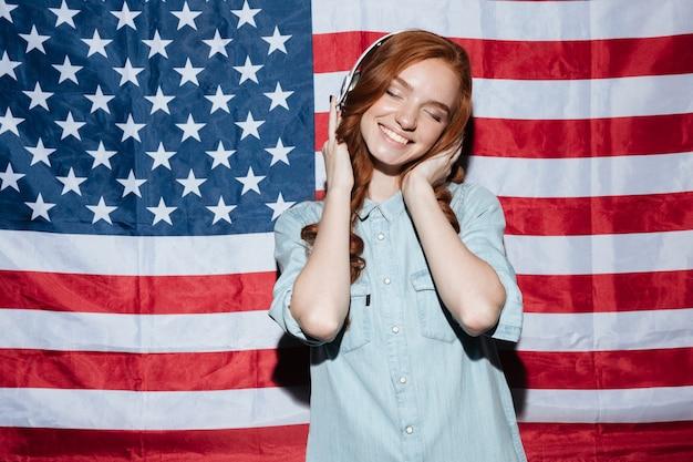 音楽を聴いて幸せな赤毛の若い女性