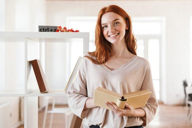 Счастливая рыжая книга чтения студента молодой леди смотря камеру.