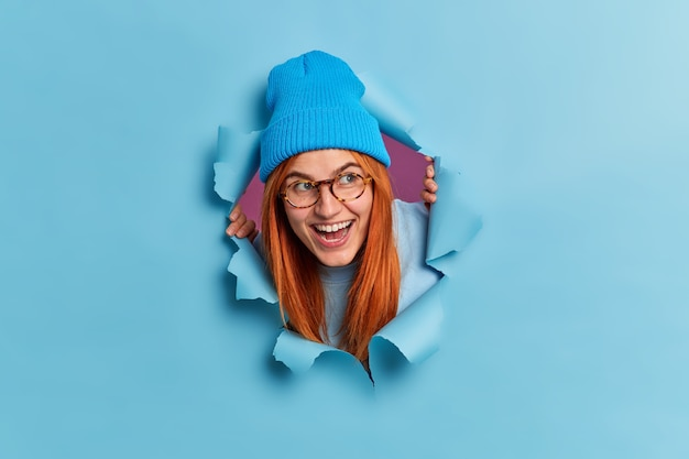 Happy redhead young woman giggles positively and looks aside has fun feels entertained wears optical glasses blue hat looks through torn paper hole