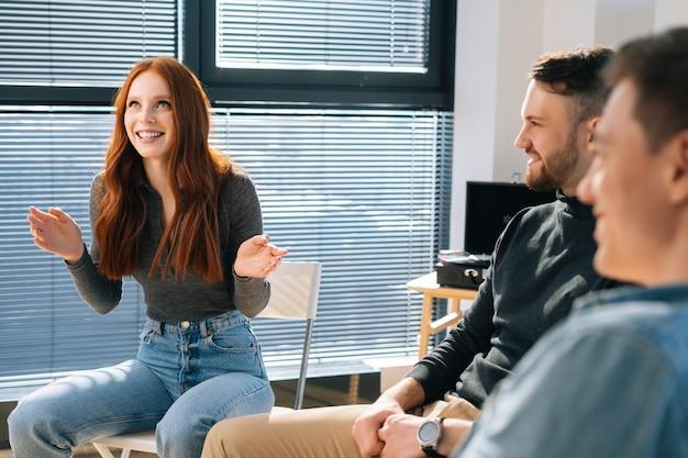 행복한 빨간 머리 젊은 여성이 창가 근처 사무실에서 창업 프로젝트에 대한 브레인스토밍을 하는 동안 창의적인 팀과 새로운 아이디어를 이야기합니다. 비즈니스 팀은 목표를 계획하고 달성하기 위해 브레인스토밍 회의를 합니다.