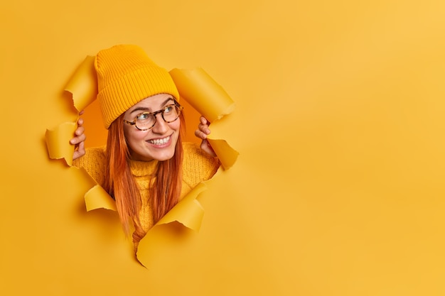 幸せな赤毛の若い女性は帽子をかぶって、眼鏡はコピースペースで陽気に脇に見えます