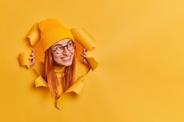 Felice giovane donna rossa indossa cappello e occhiali guarda da parte allegro in copia spazio