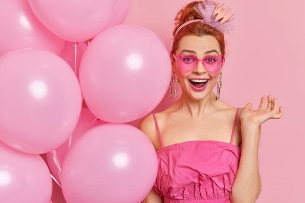 Happy redhead young woman wears trendy heart shaped sunglasses and dress holds bunch of inflated balloons celebrates birthday has positive mood isolated over pink wall. festivity concept