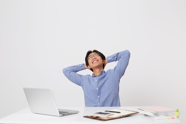 Happy relaxed asian young businessman in glasses sitting at workplace with hands over head and eyes closed and dreaming at white wall