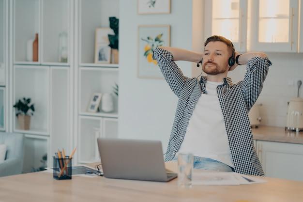 행복 한 편안한 수염 난된 남자 머리 뒤에 손을 잡고 헤드셋과 노트북, 힘든 하루 후 쉬고 남성 프리랜서를 사용하여 집에서 온라인으로 작업하는 동안 일시 중지. 원격 작업 및 프리랜서 개념