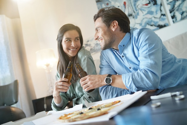 Happy relaxed couple sharing a pizza at home
