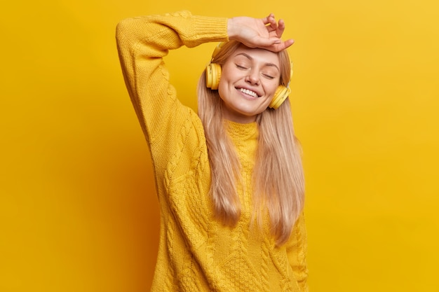 Happy relaxed european woman with long straight hair closes eyes keeps hand on forehead closes eyes in satisfaction smiles broadly shows white teeth wears casual sweater