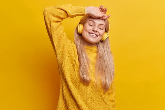 긴 직선 머리를 가진 행복 한 편안한 유럽 여자는 눈을 감고 이마에 손을 잡고 만족 미소에 눈을 감고 흰색 이빨이 캐주얼 스웨터를 입는다.