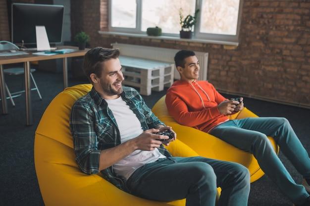 Счастливые расслабленные мужчины сидят в креслах-мешках и играют в видеоигры.