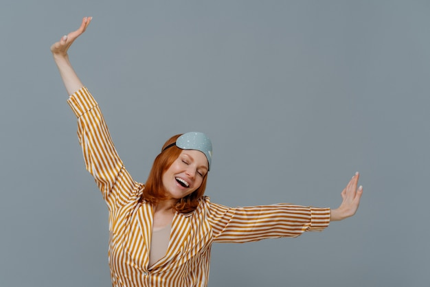 Happy relaxed red haired young woman wears comfortable soft pijamas