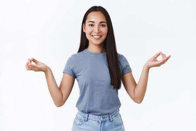 Счастливая, расслабленная улыбающаяся азиатская девушка заканчивает медитацию с помощью приложения для смартфона, открывает глаза и улыбается с облегчением и радостью, чувствует прилив энергии и позитива, держится за руки в жесте дзен, белая стена