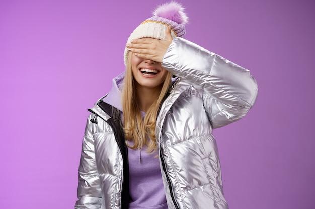 행복 하 게 웃 고 세련 된 따뜻한 실버 재킷 모자에 매력적인 젊은 금발 여자를 웃 고 손바닥 뒤에 눈을 숨기고 행복 하 게 기다리는 남자 친구가 깜짝 선물을 즐겁게 준비, 보라색 배경 서 준비.