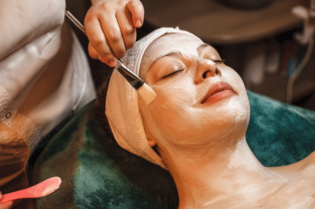 Happy relaxed woman leaning on a spa bed having a skin care white mask smiling in a wellness spa center while traveling.
