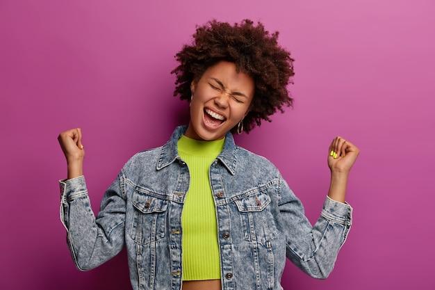 Una donna felice e rilassata alza i pugni chiusi, celebra il successo, inclina la testa, vestita con abiti di jeans, posa sul muro viola, esclama con gioia, tiene gli occhi chiusi, gode del gusto della vittoria e del trionfo