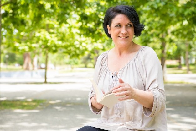 Happy relaxed woman turning pages of book outdoors