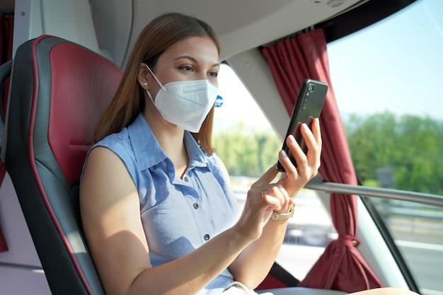 公共交通機関でスマートフォンを使用してkn95ffp2フェイスマスクで幸せなリラックスした女性。携帯電話の保護マスクのテキストメッセージでバスの乗客。輸送中は安全に旅行してください。