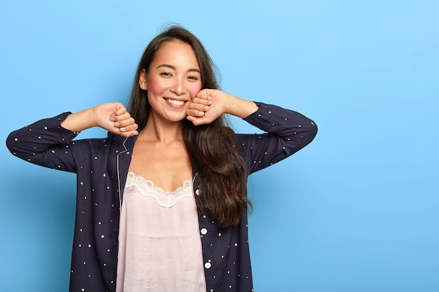 Happy relaxed young asian girl wakes up in good mood, stretches hands during morning time, dressed in nightwear
