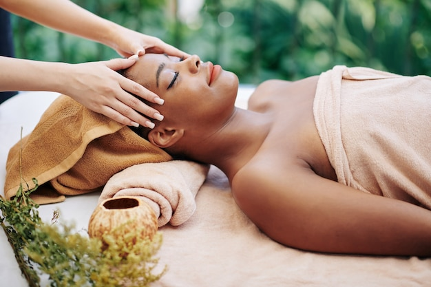 Happy relaxed young black woman enjoying head and face massage in beauty salon