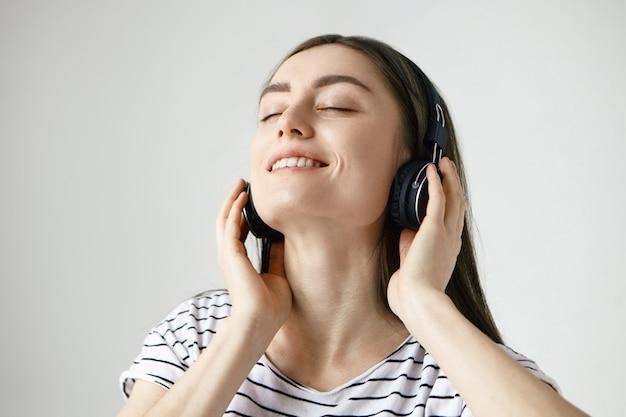 Felice rilassata giovane femmina caucasica con i capelli scuri chiudendo gli occhi e gettando la testa indietro, ascoltando musica in cuffia e ballando