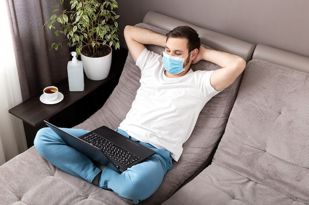 ラップトップを使用して保護マスクを着用して自宅で働く幸せなリラックスした若い白人男性。居心地の良いホームオフィス、コロナウイルス感染時のソファの上の職場19.リモートワーク