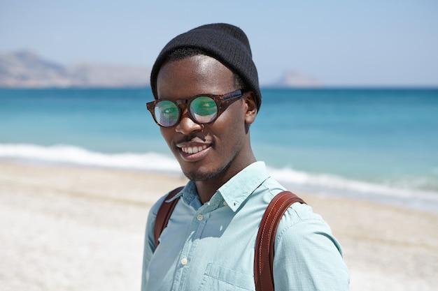 Happy relaxed young dark skinned hipster in shades and headwear standing against clear blue sky and vast azure ocean, spending summer holidays in resort town, looking with joyful smile