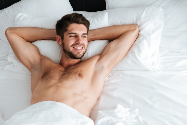 Happy relaxed young man smiling and lying in bed