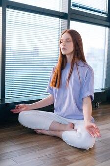 明るいオフィスルームの窓際に蓮華座で床に座って瞑想幸せなリラックスした若い女性