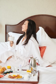 Happy relaxed young woman sitting on hotel bed in bathrobe, drinking coffee and eating breakfast
