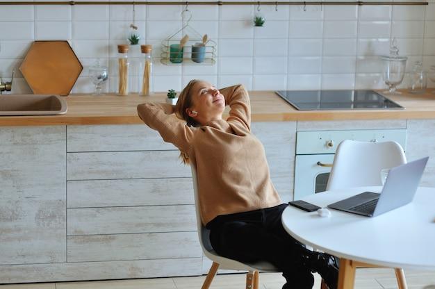 彼女の頭の上の彼女の腕を伸ばし、笑顔で窓の外を見て彼女の前にラップトップを彼女のキッチンに座って幸せなリラックスした若い女性