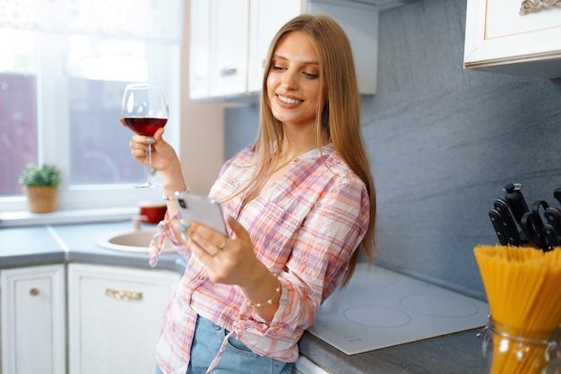 赤ワインのグラスを持ってキッチンに立って、ビデオ通話のために彼女のスマートフォンを使用して幸せなリラックスした若い女性