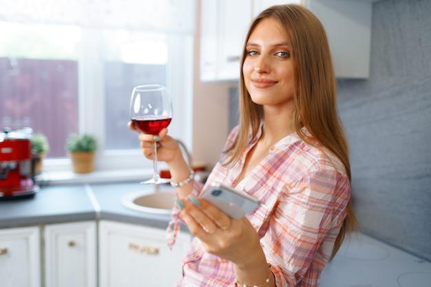 Счастливая расслабленная молодая женщина, стоящая на кухне с бокалом красного вина и использующая свой смартфон для видеозвонка