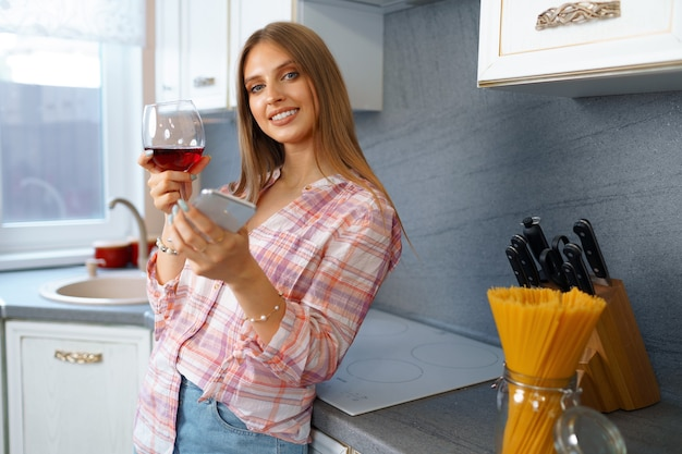 Happy relaxed young woman standing in kitchen with glass of red wine and using her smartphone for videocall