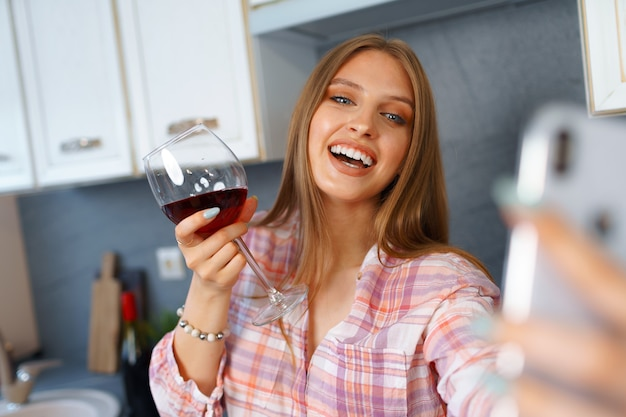 Happy relaxed young woman standing in kitchen with glass of red wine and using her smartphone