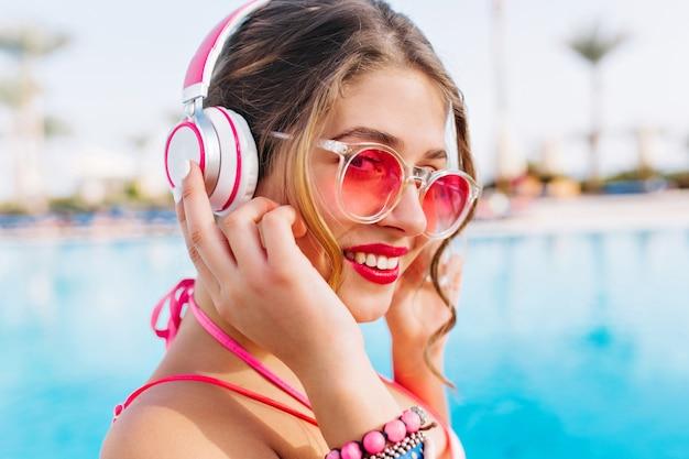 분홍색 선글라스를 통해 카메라를 찾고 이국적인 배경에 꽤 웃고 행복 편안한 소녀