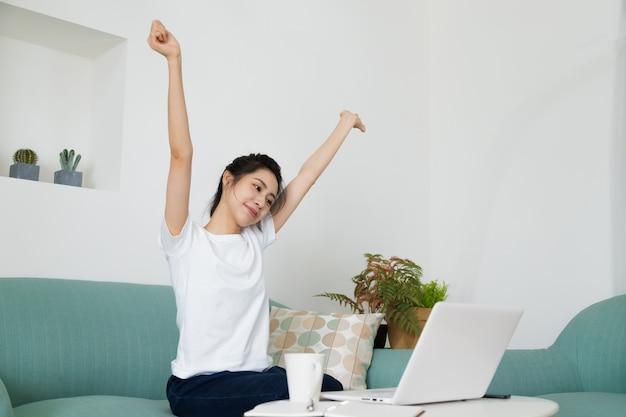 自宅のコンピューターの前でストレッチ幸せなリラックス女性