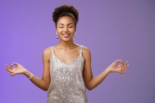 幸せな安堵したエレガントなアフリカ系アメリカ人の女性の豪華な夜の銀色のきらびやかなドレスは幸せに笑ってストレスのない落ち着きを感じ、瞑想呼吸の練習は涅槃のヨガのポーズを見つけます。