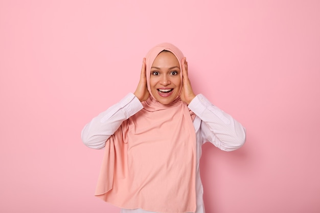 분홍색 히잡을 쓴 행복한 종교 이슬람 여성은 손으로 머리를 잡고 복사 공간이 있는 유색 배경에 격리된 놀란 표정으로 카메라를 보며 이빨 미소를 지으며 웃고 있습니다.