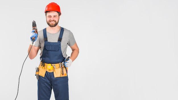 Happy repairman holding drill in hand