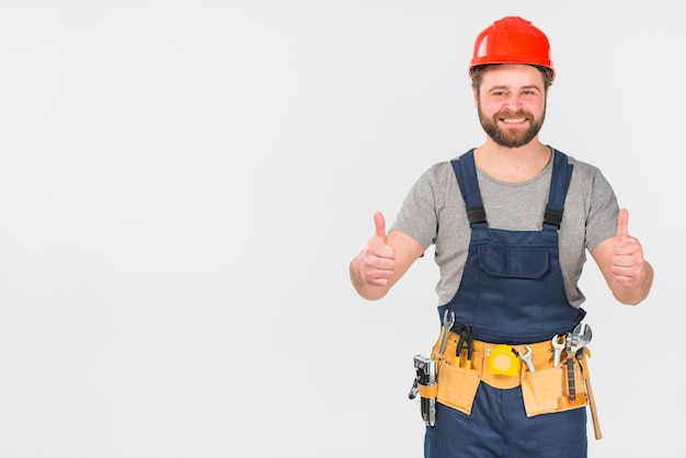 Happy repairman in overall showing thumbs up