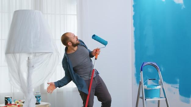 집 수리 중에 롤러 브러시로 노래하는 행복한 수리공. 파란색 페인트로 그림. 개조 및 개선하는 동안 아파트 재장식 및 주택 건설. 수리 및 장식.