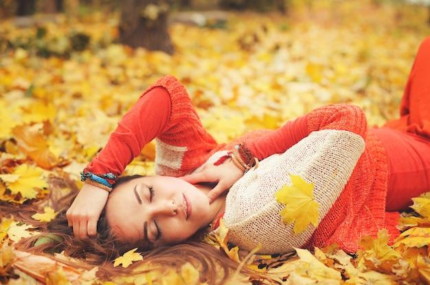 Счастливый отдыхающий портрет девушки, лежащий в осенних кленовых листьях в парке, с закрытыми глазами, одетый в модный свитер