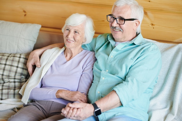 Happy retired couple in casualwear sitting on couch in front of tv set and watching movie or program at home