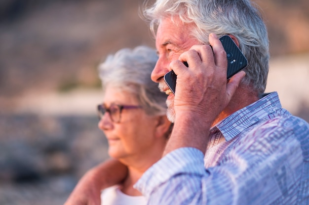Happy retired couple of caucasian man and woman people hug and look in front of them using and speaking with modern smart technology phone - modern lifestyle for old adults