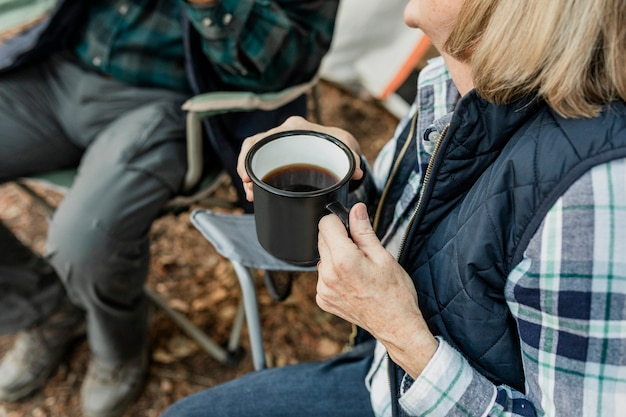 Happy retired couple having coffee by the tent in the forest