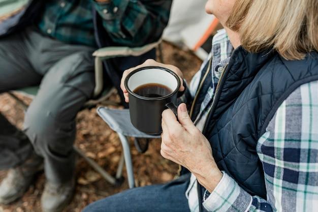Счастливая пара пенсионеров, пьющих кофе у палатки в лесу